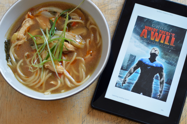 A Bowl of spicy chicken soup with a Kindle. The cover on the screen is Where There's A Will by Cari Z.