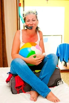 Girl on suitcase ready to go on vacation. We need to not pack our bags too soon.