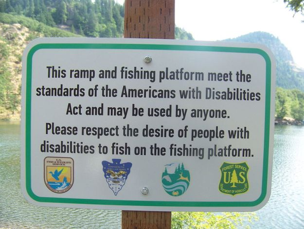 "A sign in the foreground reads ""This ramp and fishing platform meet the standards of the Americans with Disabilities Act and may be used by anyone. Please respect the desire of people with disabilities to fish on the fishing platform. In the background is a lake surrounded by trees."