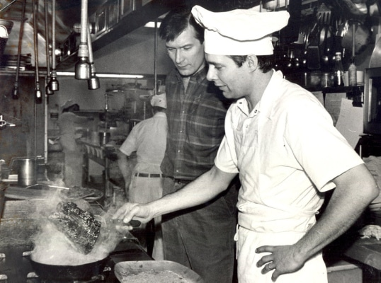 TIMES-SHAMROCK ARCHIVES In the kitchen at Cooper's Seafood House, Mark Cooper blackens a red fish as his brother, Jack, watches on March 8, 1986.