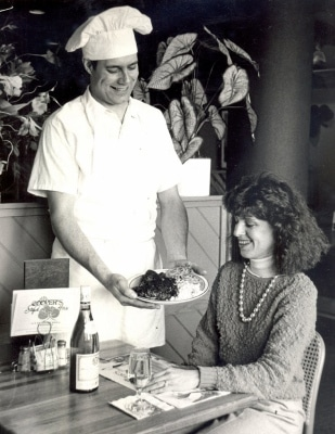 TIMES-SHAMROCK ARCHIVES Mark Cooper serves a blackened red fish to his brother, Jack Cooper's, wife, Angela Menichillo Cooper, on March 8, 1986.
