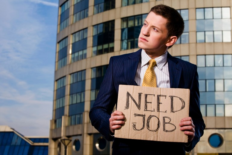 Financial crisis. Unemployment. Young businessman holding sign Need Job outdoors