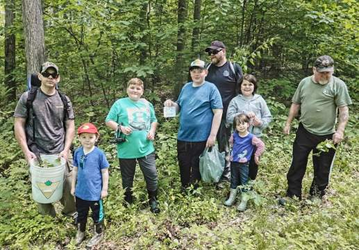 a group of volunteers pose in the copeland forest where they were helping pull the garlic mustard plants