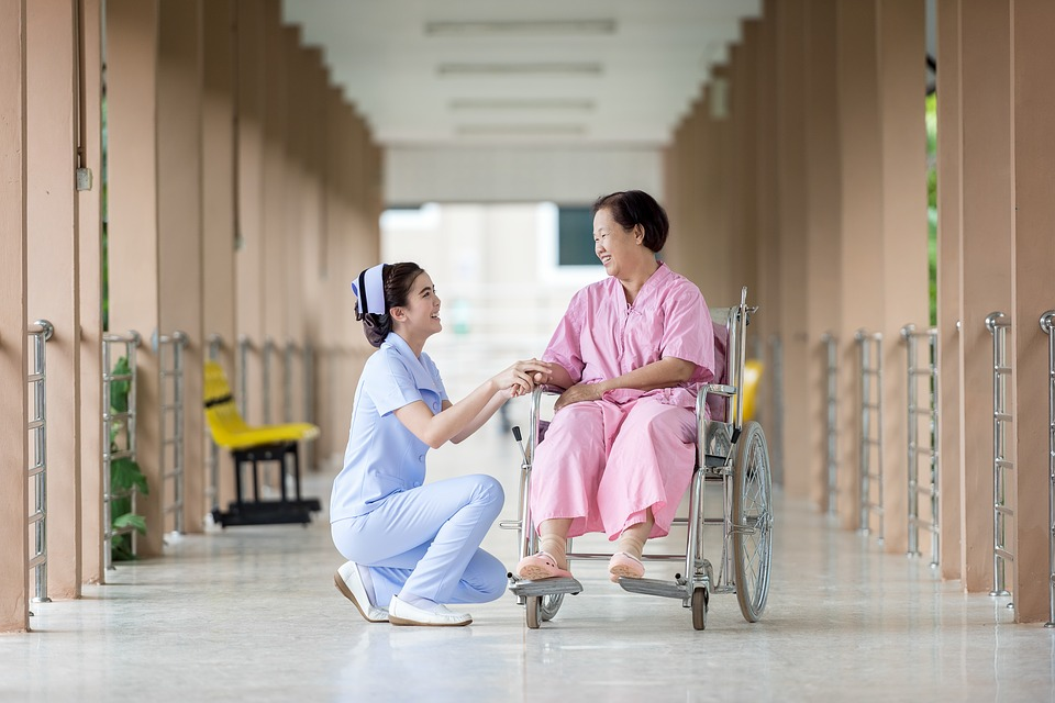 Nurse talking to a patient sitting on a wheel chair