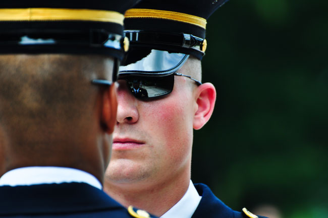 Sgt. Benton Thames inspects a sentinel before the sentinel begins his walk on the mat at Arlington National Cemetery.
