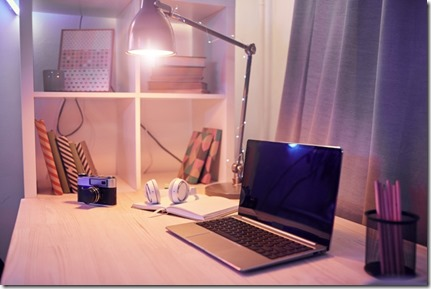 Image of workplace with laptop computer note pad and camera are on the table with electric lamp at domestic room
