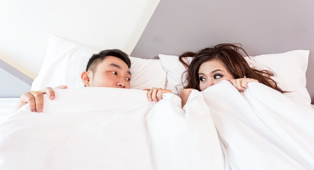a man and a woman under a white blanket in the bedroom