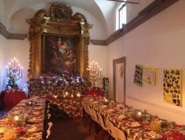 luci accese sulla grande tavolata di natale del punto di ristoro sociale comune caritas