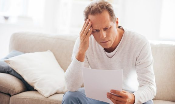 Depressed mature man holding paper and looking at it while sitting on the couch at home