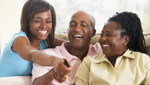 Family Watching Television Together Arguing Over Remote