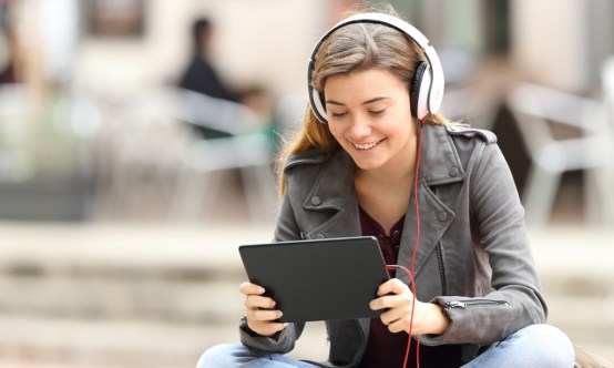 Beautiful fashion girl is learning online with a tablet and headphones sitting on a bench in the street.