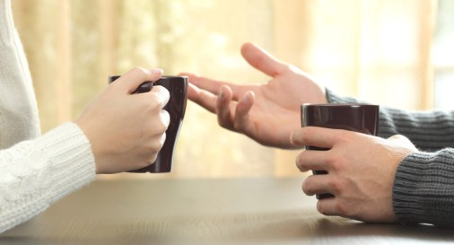 Back light profile of hands of 2 friends or couple talking holding coffee cups sitting in a table at home with a window in the background