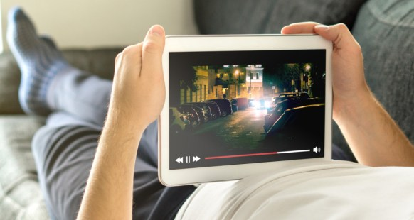 Online movie stream with mobile device. You see movies on tablet with imaginary video player service.