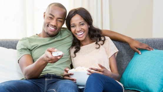 couple sitting on couch watching tv
