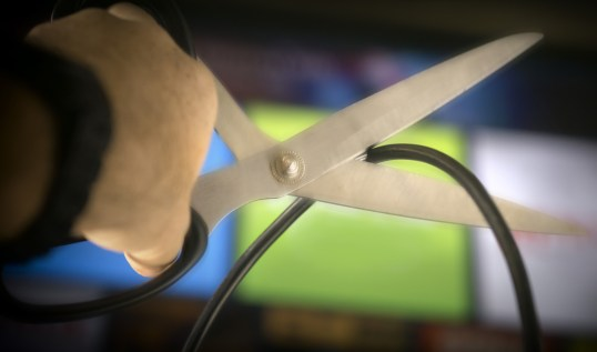 man cutting cord with scissors