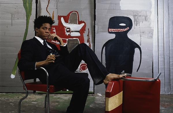 Basquiat seated in front of mural