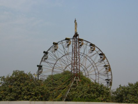 A giant ferris wheel stick out above the treetops in the distance