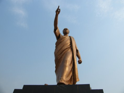 The memorial statue with the right hand pointing upward toward the blue sky in Kwame Nkrumah Mausoleum and Memorial Park