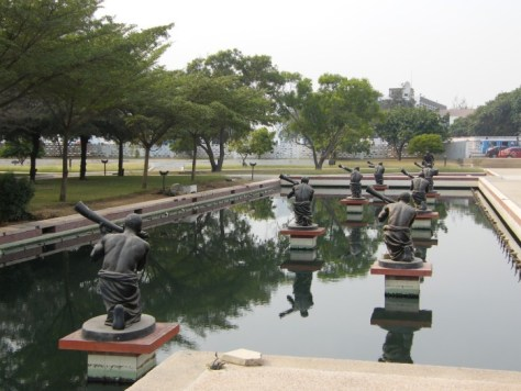 Many statues of rowers in a long pond in Kwame Nkrumah Mausoleum and Memorial Park