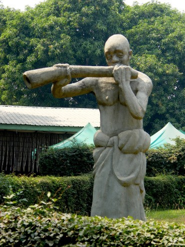 A sculpture of a man playing a bull horn-type instrument near the entrance of the Ghana's national museum