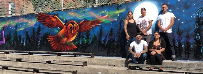 The artists pose in front of their mural