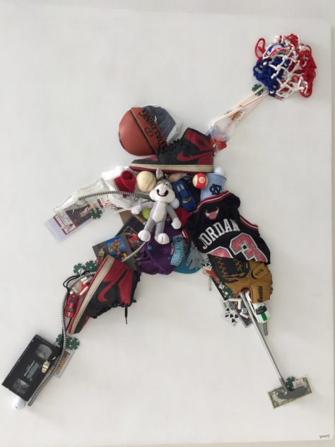 A basketball and other objects glued to a painted wood panel to form a jumping man dunking a basketball