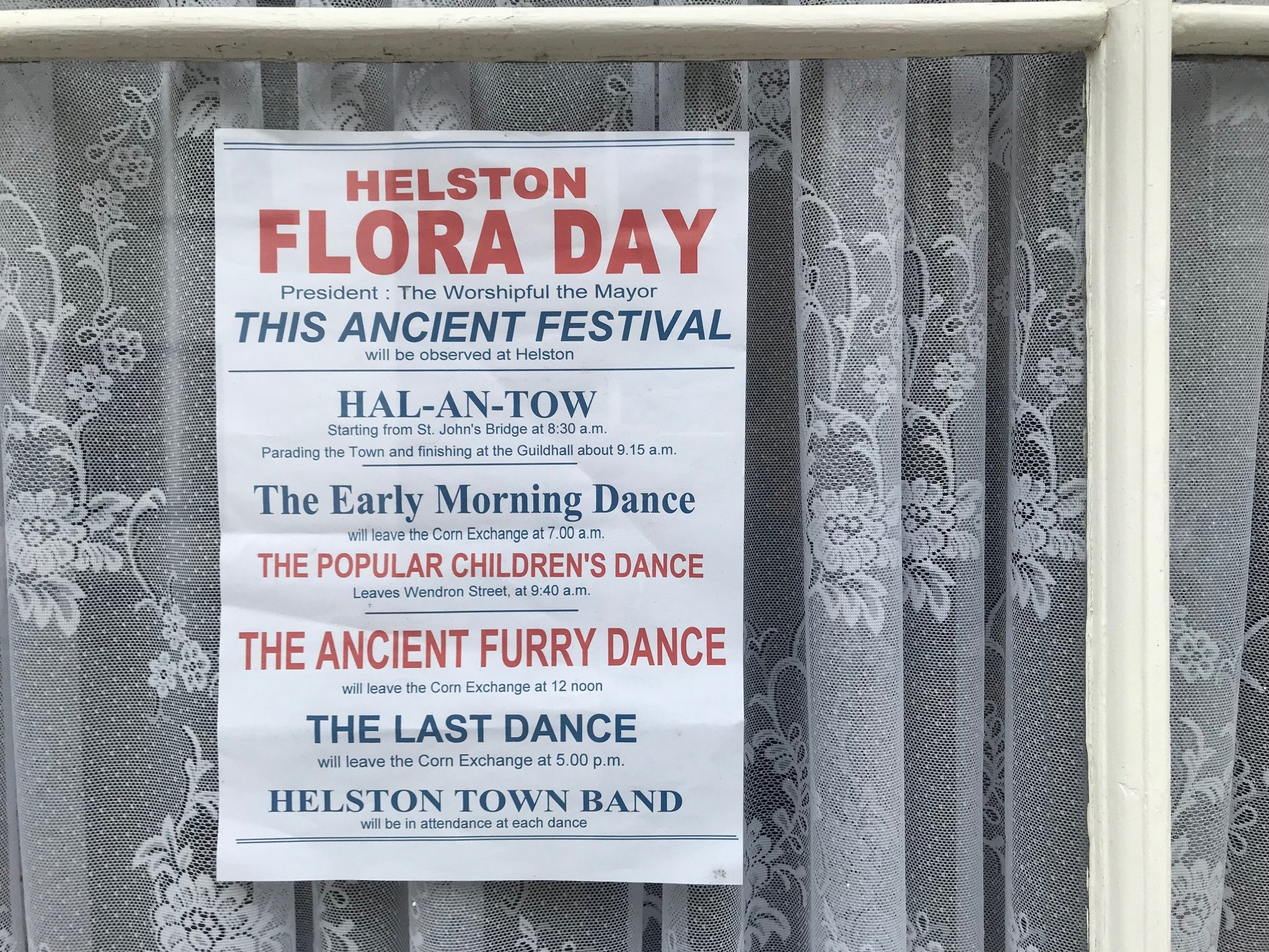 Poster advertising events of Flora Day in a house window. Printed red and blue text on a blue poster.