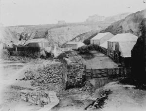 A view of Treffry fish cellar, above Towan Beach, with the buildings and cliff behind. Treffry was built around 1845 and was located in the middle of Towan Promenade. It was also known as the 'Flour and Fat' although it is not known where the  cellar got this nickname from. The cellar's huer was William Osborne, the master seiner was Isaac Pappin and the agent was Thomas Jenkin. Photographer: Unknown.