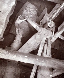 Miners here stand on narrow beams as they arrange machinery