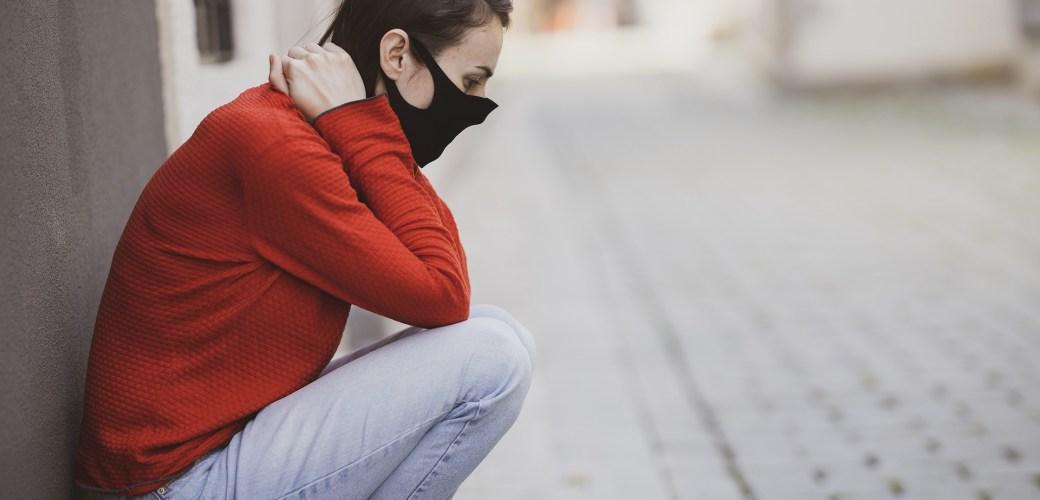vrouw hurkend met handen in nek buiten draagt masker