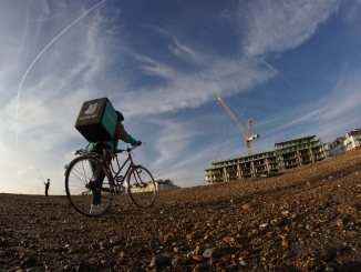 A Deliveroo driver treks into a construction site. Those working for Deliveroo and other gig economy companies like Uber and Amazon should be classified as workers, says a report by the Work and Pensions Committee.