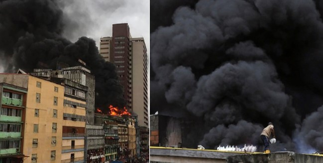 Man tries to put out violent fire at Balogun market with bucket of Water (Video)