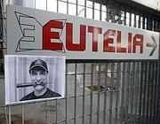 Una foto dell'ex amministratore delegato di Eutelia Samuele Landi attaccata al cancello d'ingresso dell'azienda (Ansa)
