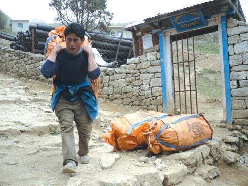 Un ragazzo con un sacco di spazzatura raccolto in vetta