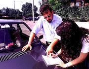 Due automobilisti compilano una constatazione amichevole dopo un sinistro (Fotogramma)