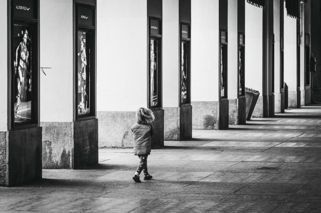 Bambina che passeggia da sola sotto i portici di Via Po a Torino