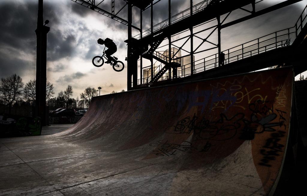Ciclista salta dalla rampa di una pista da skateboard al tramonto