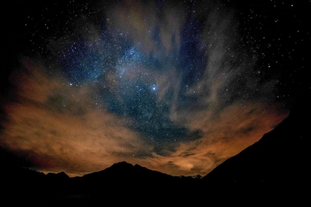 Paesaggio montano con cielo stellato e nuvole colorate dal tramonto