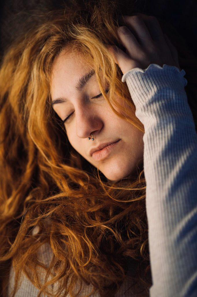Fotoritratto di una ragazza con occhi chiusi e capelli rossi