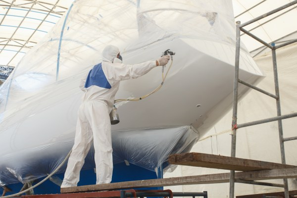 Man spraying paint to the boat
