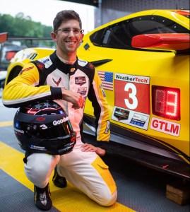 Jordan Taylor kneels beside the No. 3 Corvette along with his Dale Earnhardt tribute helmet (Jamey Value)