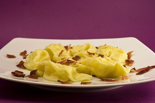 Tortelli con ripeino di patate e monte veronese allo speck croccante