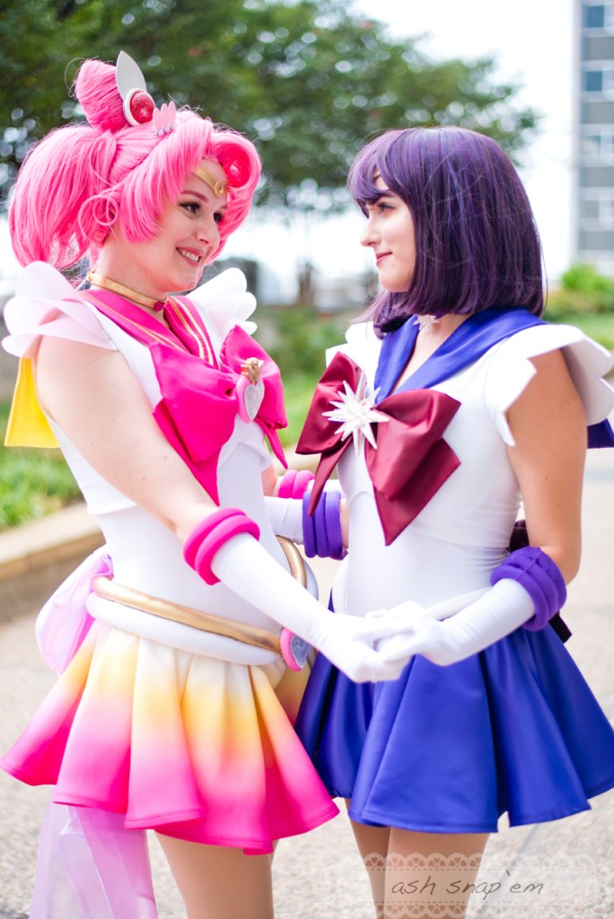 Cosplayers Pocky Pants and Pocket Cos hold hands and smile at each other as Super Sailor Chibi Moon and Sailor Saturn.