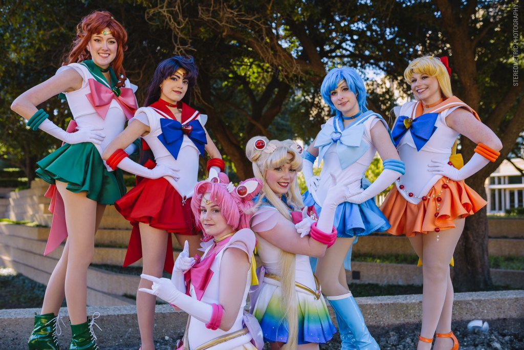 Cosplayers from left to right, Reid as Super Sailor Jupiter, Koholint as Super Sailor Mars, Pocky pants as Super Sailor Chibimoon, Dani Rene as Super Sailor Moon, Wendykuma as Super Sailor Mercury, and Space Cadet as Super Sailor Venus pose in a V formation with hands on hips, with the exception of the Moons posing in the trademark Punishment stance.