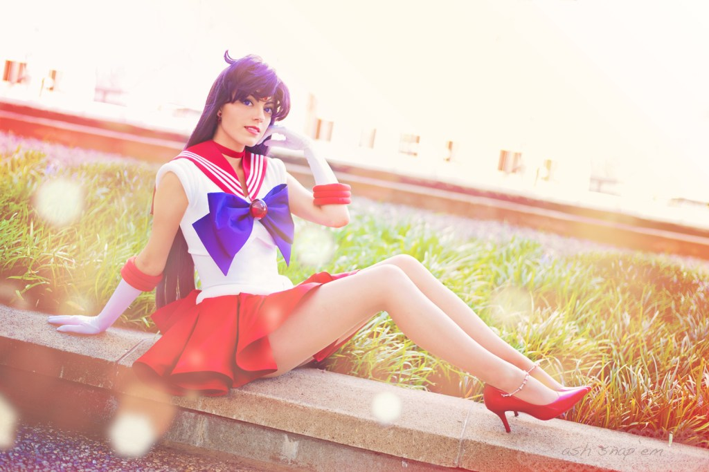 Cosplayer Koholint sits posed with her knees up and one hand by her face as Sailor Mars.