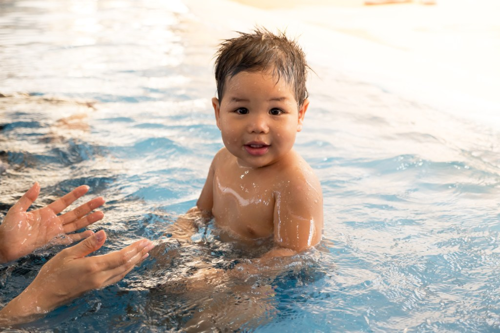 Toddler sitting in swimming pool shallow water