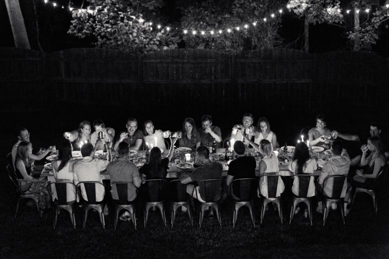 Nightime party with signature farm table