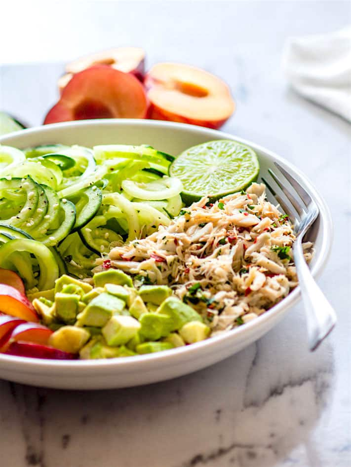 Power Lunch Paleo Asian Crab and Avocado SPiralized Cucumber Salad! Light, Gluten Free, and Super Healthy crab and zesty spiralized cucumber salad topped with avocado and juicy plum. Asian style crab salad that makes for a great protein packed and nutrient dense lunch, appetizer, or main meal. @cottercrunch