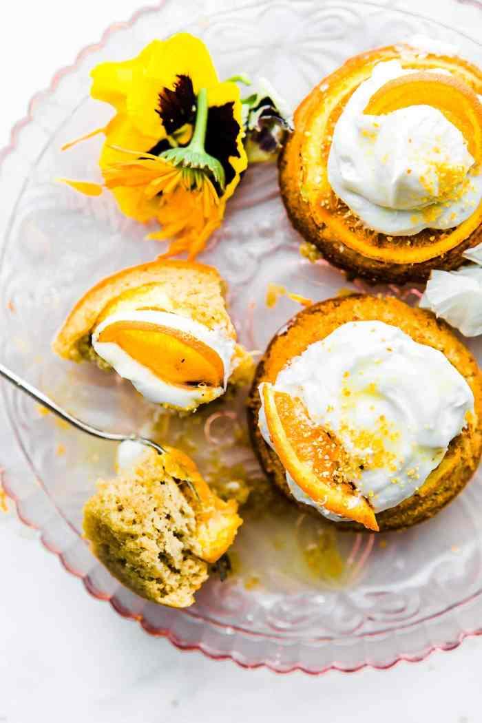Orange Mini Paleo Upside cake (cakes) with cream on plate with fork.