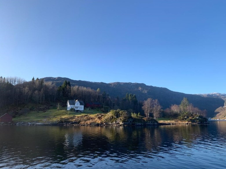 small white cottage on the shore by a lake, blue sky